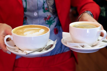 Two cups of coffee in female hands, cafe, spending time.