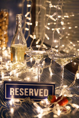 Closeup strawberry, two crystal glasses, bottle champagne sparkling wine, reserved nameplate on wooden table, window, garlands. Concept date evening in restaraunt, 8 march, Valentine's Day, christmas