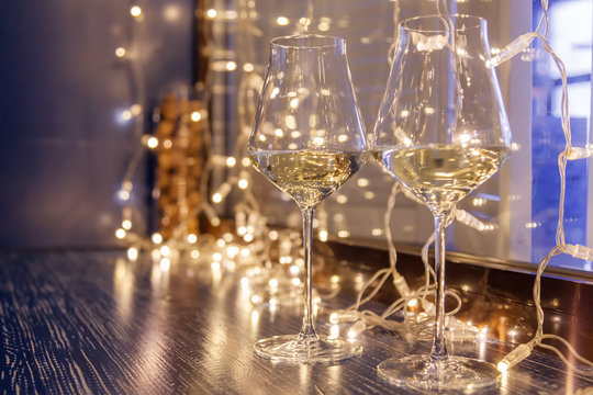 Closeup of two glasses of white wine in transparent crystal glasses on background of window and garlands. Concept romantic dinner in Michelin premium restaurant, party, February 14, March 8