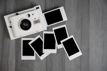 Vintage instant photo camera with blank polaroid photos with copy space on wooden table