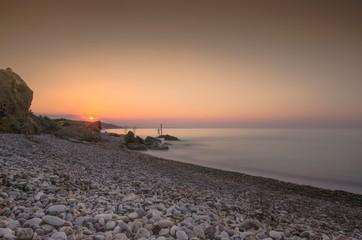 Bellissimo paesaggio marino con spiaggia di sassi al tramonto