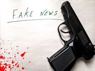 writing on a piece of paper, fake news, blood on a piece of paper, false news, journalism, a gun on a piece of paper and blood
