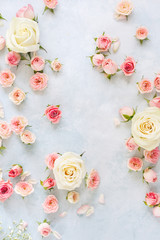 Various roses, petals  and buds on light blue textured background. Women's Day,  greeting card or wedding invitation, copy space