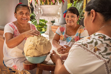 Women making Tortillas. Group of smiling cooks preparing flat bread tortillas in Yucatan, Mexico