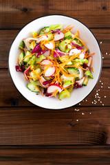Healthy vegetarian vegetable salad with fresh raw radish, carrot, celery, lettuce, sesame and flax seeds. Vegan diet food