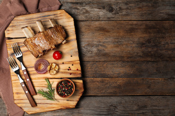 Flat lay composition with roasted ribs and space for text on wooden background. Tasty meat