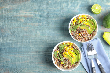 Healthy quinoa salad with vegetables in bowls served on wooden table, top view. Space for text