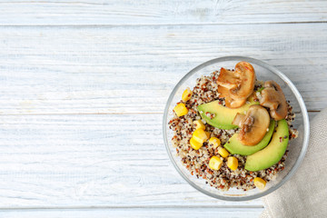 Healthy quinoa salad with vegetables in bowl on wooden table, top view. Space for text