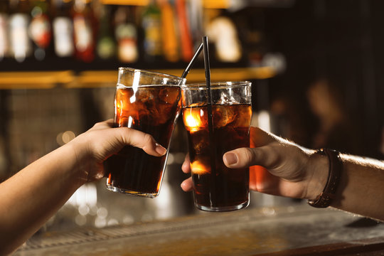Young couple with glasses of cola in bar, closeup