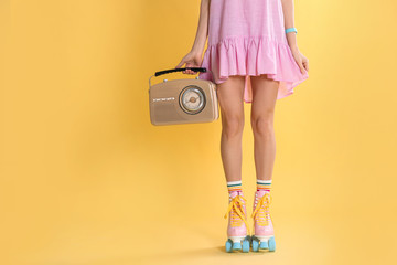 Young woman with roller skates and retro radio on color background, closeup. Space for text