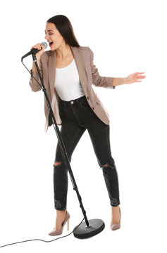 Young stylish woman singing in microphone on white background