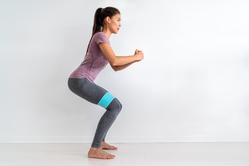 Resistance band fitness woman doing squat exercise with fabric booty band stretching strap. Crab walk squatting workout girl training at home.