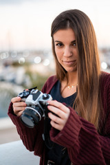 Beautiful smiling woman holds a retro camera