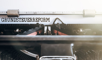 German word Grundsteuerreform (property or land tax reform) written on old typewriter