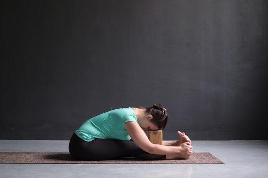 woman practicing yoga, Seated forward bend pose, using brick or block