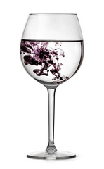 Glass with water and drop of violet ink. Half full glass for wine isolated on white background with clipping path.