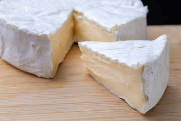 Tasty blue cheese on a wooden board. Prepared Italian dishes on the kitchen table.