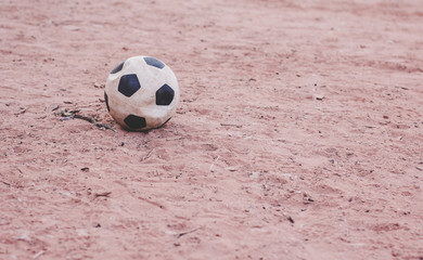 sport in poor Middle East countries concept wallpaper pattern background photography concept of deflated football ball on a sand with empty copy space for your text or inscription