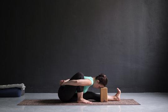 Young woman practicing yoga asana amarichyasana indoors