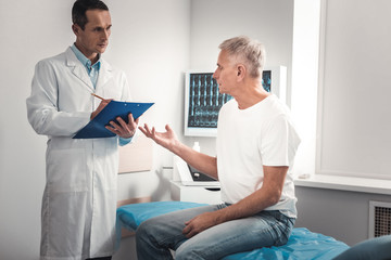 Grey-haired man asking the doctor about further checkups
