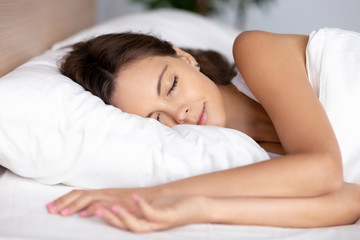 Serene calm young woman sleeping well on orthopedic soft pillow under warm duvet in comfortable cozy fresh bed having good night peaceful healthy sleep enjoying nap dreams resting enough concept.
