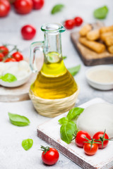 Fresh Mozzarella cheese on vintage chopping board with tomatoes and basil leaf with olive oil and tray with cheese sticks on stone kitchen table background.