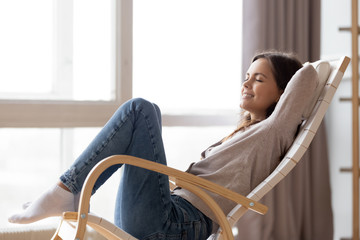 Relaxed calm young woman lounging sitting in comfortable wooden rocking chair breathing fresh air dreaming, happy lazy girl chilling relaxing enjoying no stress free peaceful quiet weekend at home