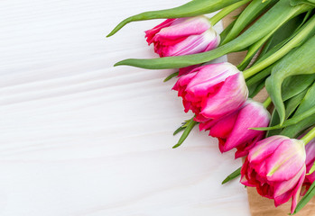 Red tulips on white wooden background. Copy space.