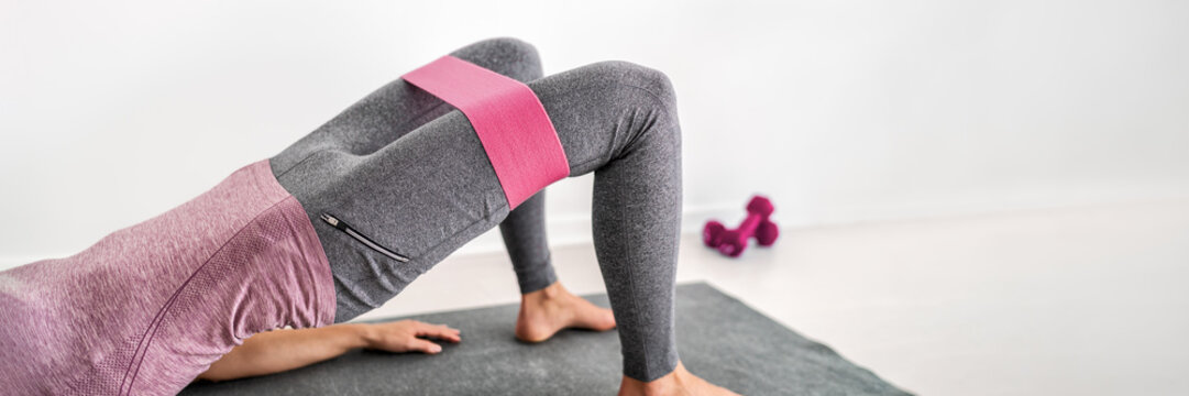 Fitness resistance band glute bridge with hip abduction exercise woman workout at home. Fit girl training with circle hoop booty bands for glute strengthening banner panorama.
