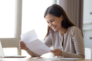 Happy excited woman student customer reading letter with good news, great cheap offer, get job opportunity, scholarship admission, loan approval, money refund holding paper mail bank statement