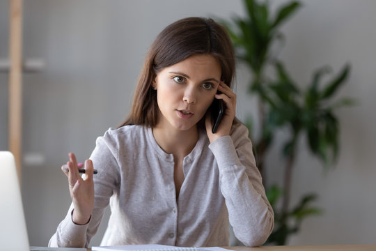 Serious focused manager consulting client talking on the phone making business call at work, young female worker or customer speaking by mobile complaining on service or explaining solving problem