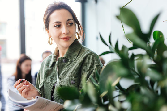 Woman stand at office surround with green plants and write at her note book