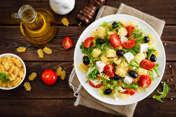 Italian pasta salad with fresh tomato, cheese, lettuce and olives on wooden background. Mediterranean cuisine. Cooking lunch.  Healthy diet food