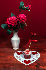 Beautiful pink roses in a vase, heart shapped white dollie with a decorated cup cake on it with a heart on a pick.