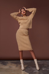 Sexy beauty woman pretty face tan skin wear beige knitted suit dress long skinny body shape makeup cosmetic summer collection studio catalog brunette accessory clothes for office party fashion shoes.