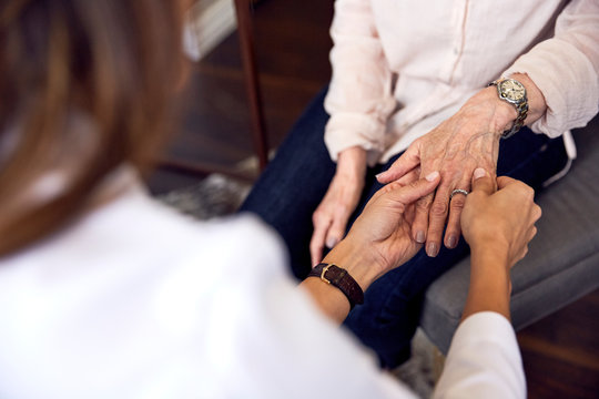 female doctor examining older woman hand