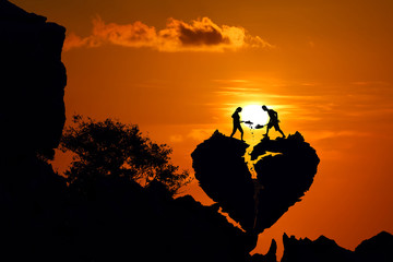 Couple on the broken heart shape rock on the mountain with red sky sunset