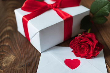 Beautiful red rose on a dark wooden background. White envelope with a red heart. White gift box tied with a red ribbon. Valentine's Day. March 8. Mothers Day. holidays. birthday. Santa. new Year. Chri