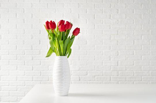 Red tulips in white vase against white bricks background