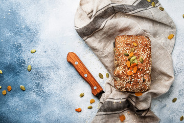 Whole wheat organic rye dark bread with pumpkin seeds, dried fruit, raisins and sesame seeds on gray towel on the kitchen table background, top view. Space for text