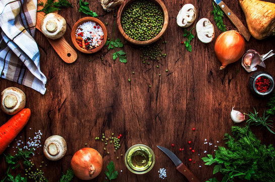 Ingredients for cooking green lentils with mushrooms and vegetables, spices and herbs, vintage wooden kitchen table background, place for text. Vegan or vegetarian food, clean food concept