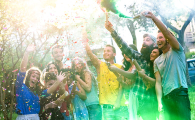 Happy millennial friends having fun at garden party with multicolored smoke bombs outside - Young millenial students celebrating spring break fest together on genuine youth concept - Focus on confetti