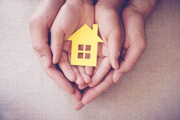 Adult and child hands holding yellow house, family home and homeless shelter concept