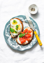 Healthy breakfast, snack, tapas - sandwiches with cream cheese, boiled egg and smoked salmon on a light background, top view