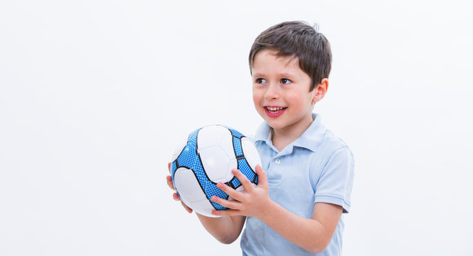 Boy playing with soccer ball, isolated on white studio background. Portrait of kid football player with ball in hand. Young cute male holding sport equipment. Education conceptual picture.