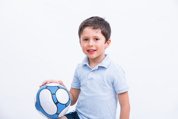 Happy boy playing football. Cute child, young male teen goalkeeper enjoying sport game. Little footballer holding ball, isolated portrait on white background. Kid having fun from sport activity.