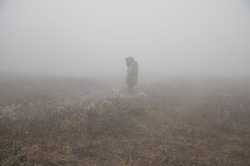 silhouette of a child standing in the foggy field. covered in mist