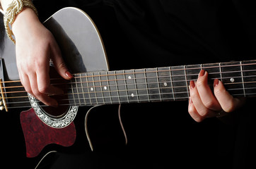 Female hands playing guitar