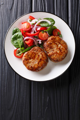 French meat balls crepinette served with fresh vegetable salad close-up. Vertical top view