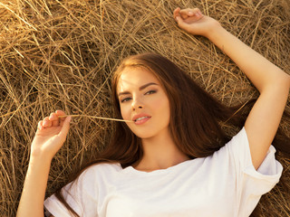 Beautiful young woman is relaxing on the haystack.